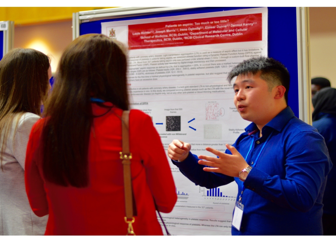 "Louis Richter, a medical student from RCSI, presents his research entitled ""Patients on aspirin: Too little or too much?"" to a committee of judges during a poster session at ICHAMS 2016."