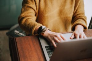 Person wearing a yellow jumper typing on a laptop