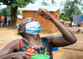 A woman in a rural area has her head tilted back as she holds a medicine tablet over her mouth. In her other hand she holds a tumbler of water.