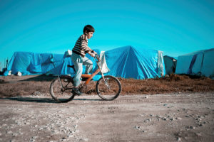 A child rides a bike past tents of a refugee camp